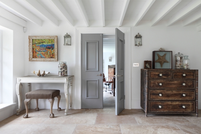 salon rustique qui joue sur le contraste des pièces du mobilier foncées et claire où la porte interieure constitue un élément harmonisant