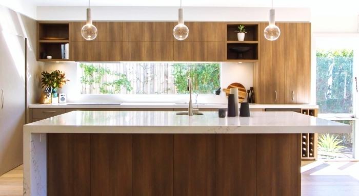 modele de cuisine moderne au plafond blanc et parquet de bois clair avec ilot central en bois foncé et comptoir blanc design marbre