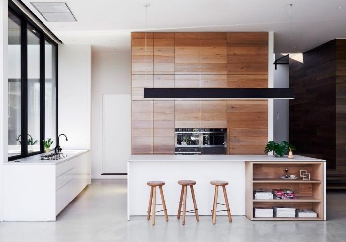 exemple design intérieur moderne dans une cuisine blanche avec pan de mur en bois brut et ilot central blanc et bois