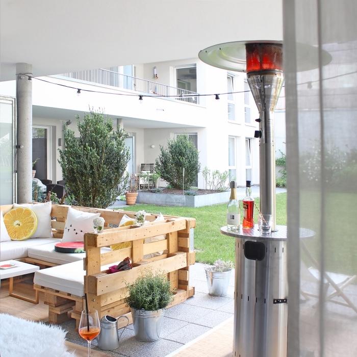 patio ou déco jardin avec salon de jardin en palette sur plancher de bois et carrelage gris décoré avec plantes et coussins