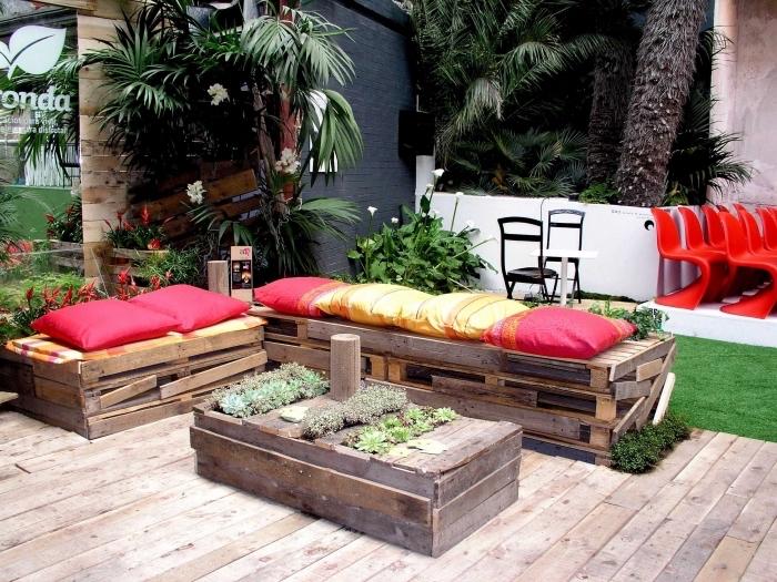 ambiance estivales dans un jardin au plancher de bois aménagé avec meubles en palette à design récup et plantes vertes