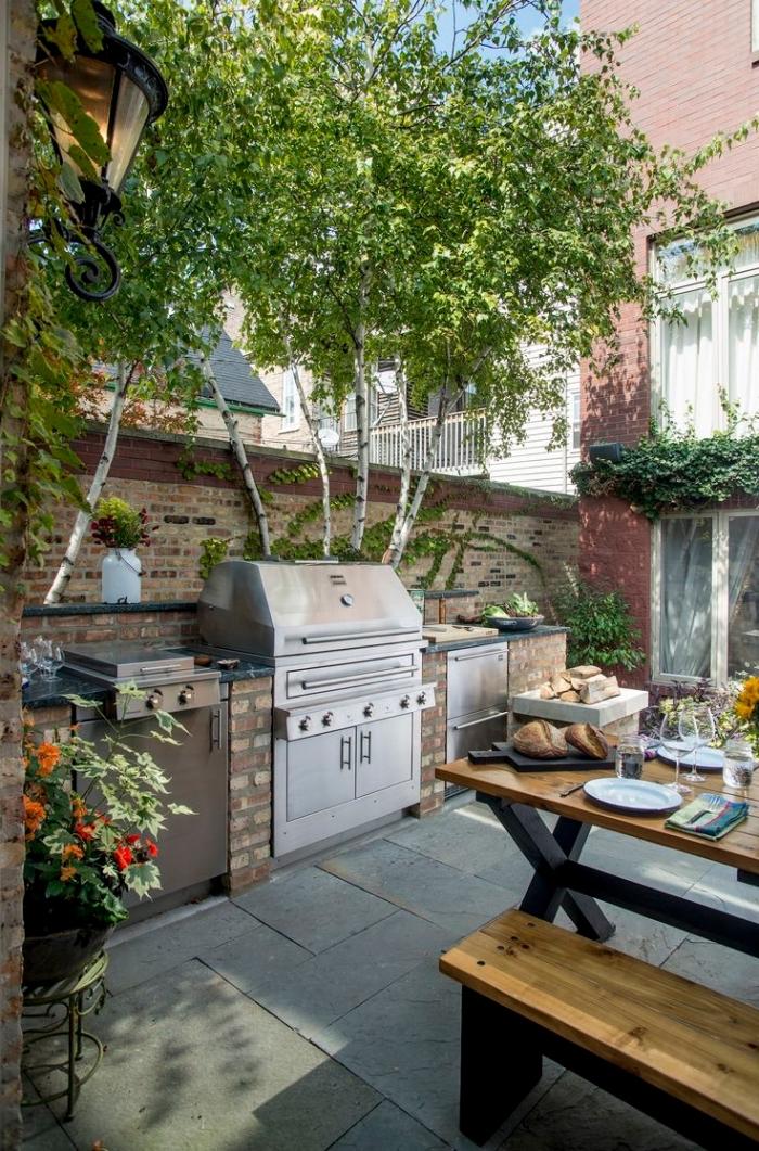déco de cuisine ouverte dans le jardin avec ilot en pierre et équipement barbecue en acier inoxydable, table à manger bois et noir