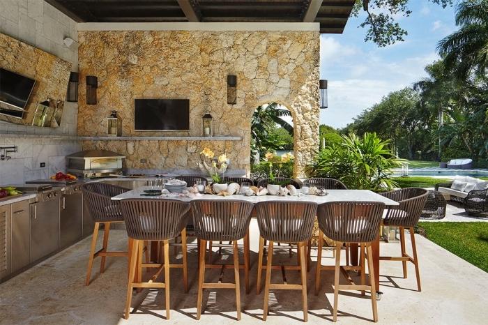 déco de cuisine ouverte vers la piscine avec toit de bois solide et mur en revêtement pierre, cuisine d'été avec crédence en carrelage blanc