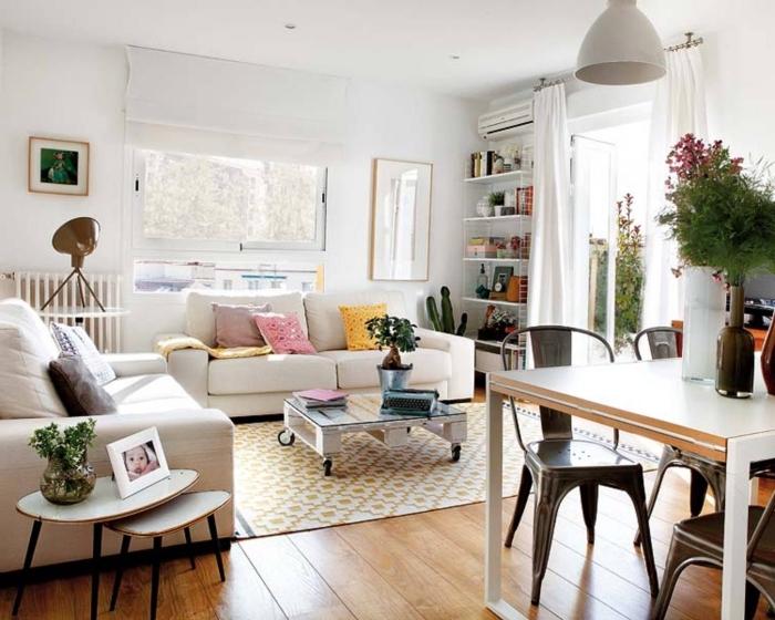 une table basse palette peinte en blanc avec un plateau en verre, et d'une structure allégée qui s'harmonise avec l'intérieur blanc du salon scandinave moderne