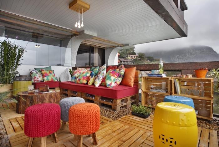 idée pour meuble en palette facile à réaliser soi-même, canapé et banc en palette décorés avec coussins multicolore aux motifs géométriques et tropicaux