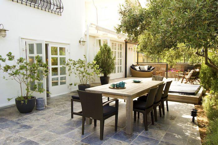 salle à manger extérieure en table et chaises bois, terrasse bois pour aménager un coin détente en chaises bois et canapé rotin, coussins décoratifs