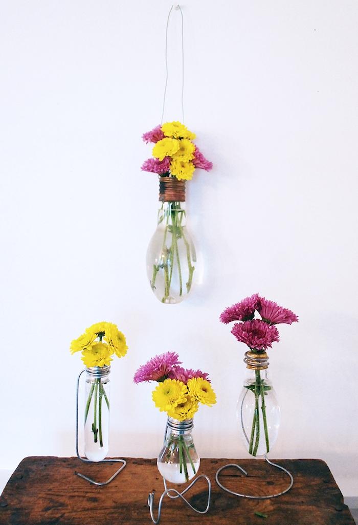 idées loisirs créatifs adultes, ampoule electrique transformée en vase avec de petits bouquets de fleurs à l intérieur, table bois brut