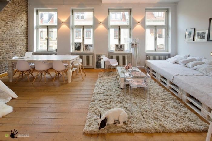 un loft lumineux scandinave aux accents bruts aménagé avec des meubles en palettes, petite table basse palette assortie avec une chaise transparente