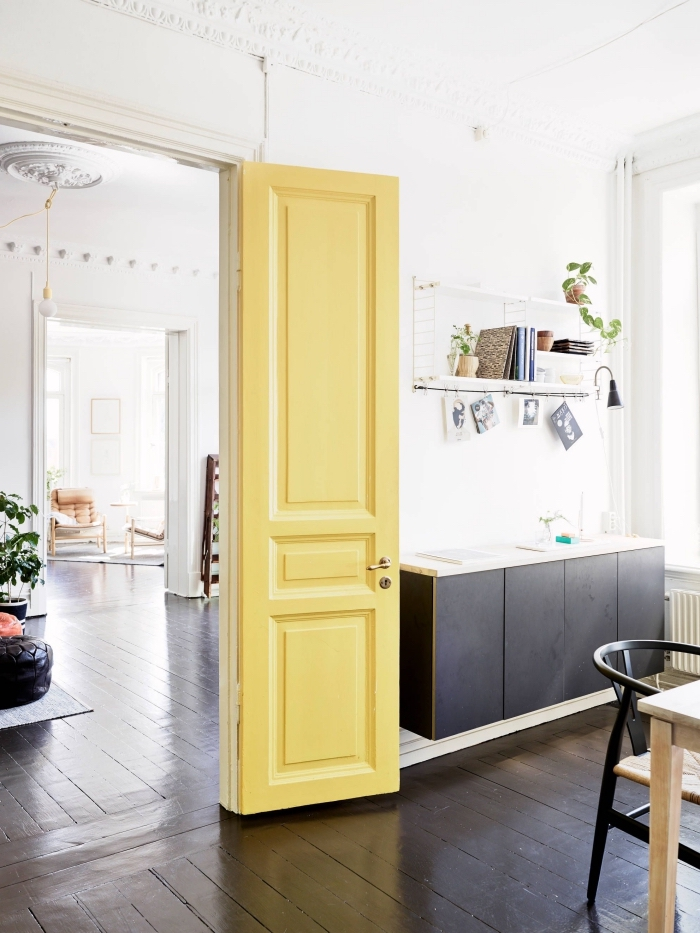une porte d'intérieur repeinte en jaune citron pour créer un accent coloré dans l'ambiance minimaliste de cet appartement scandinave