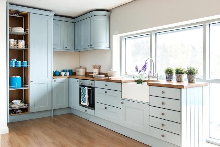 déco de style vintage dans une cuisine blanche avec meubles de bois peint en bleu pastel et comptoir de bois brut