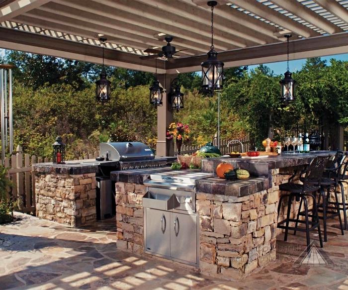 exemple de cuisine d été couverte avec toit en bois et lampadaire noirs, cuisine extérieure avec ilot en pierre