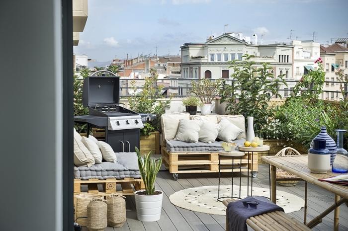 idée comment décorer une terrasse au plancher de bois gris avec mobilier en palette DIY et plusieurs coussins décoratifs