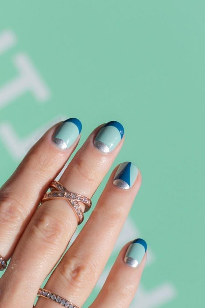 idée pour faire une manucure de base vert clair avec bouts en bleu foncé et effet demi-lune en lunule argent métallique