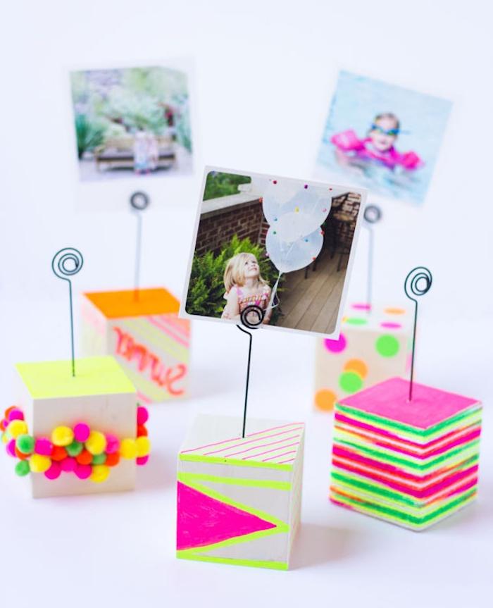 porte photo en block de bois coloré au feutre et petits pompons colorés avec une accroche en fil de fer pour poser des photos