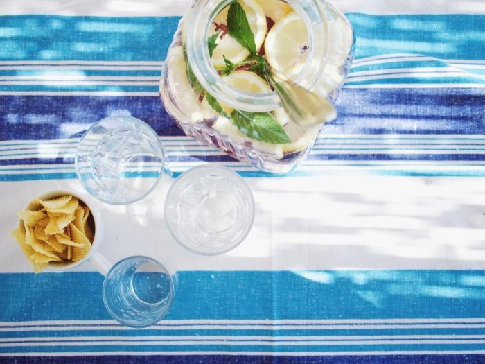 recette jus de fruit classique avec eau et agrumes, pichet citronnade à la base de jus de citron et feuilles de menthe