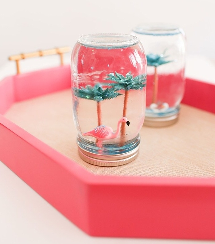 exemple d activité manuelle facile et rapide pour fabriquer une boule à neige été avec figurines palmiers et flamant rose