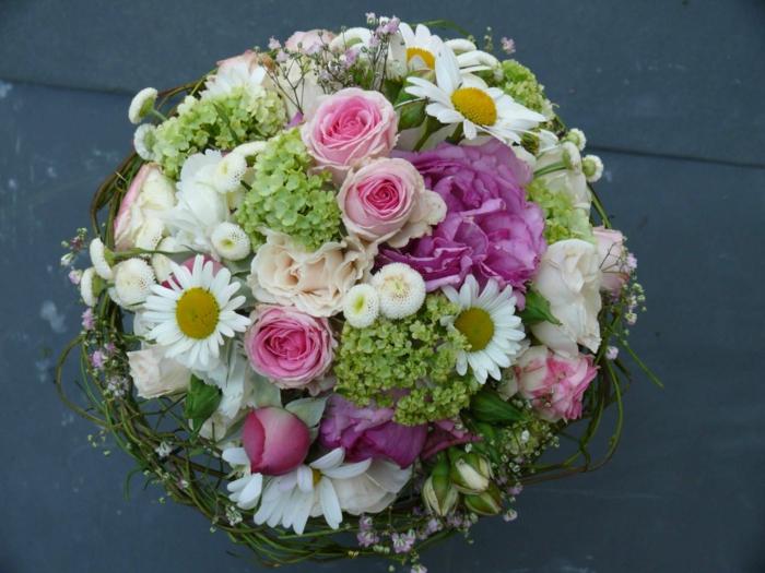brindilles vertes qui entourent un joli bouquet de fleurs, roses, pâquerettes et hortensias