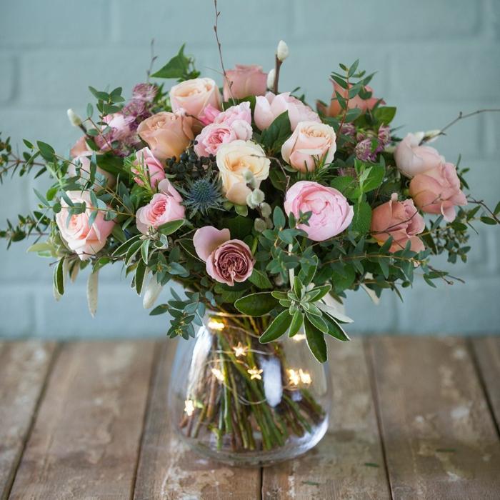 vase en verre, guirlande lumineuse et grand bouquet de roses pastels, plusieurs brins verts