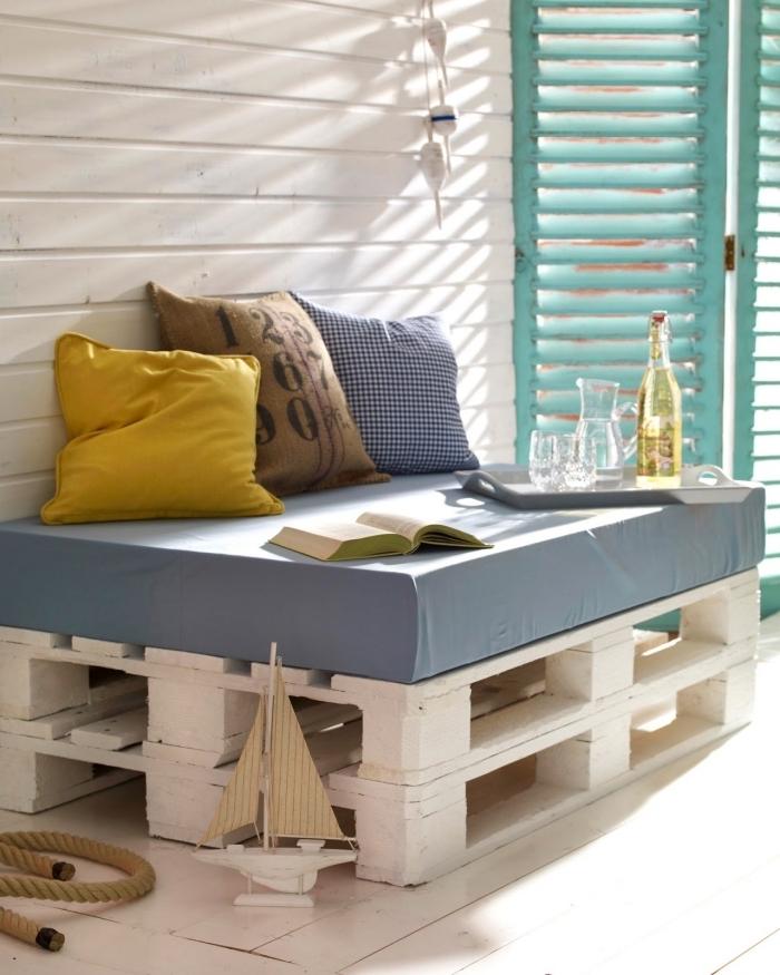 ambiance marine sur une véranda à façade blanche et portes volets turquoise aménagée avec meuble place assise en bois