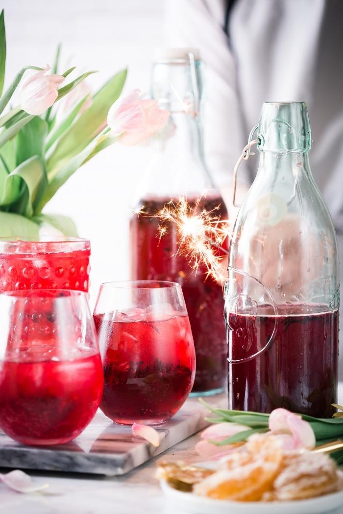 décoration de table avec bouquet de tulipes roses et boisson rafraîchissante aux fruits rouges servie avec glaçons