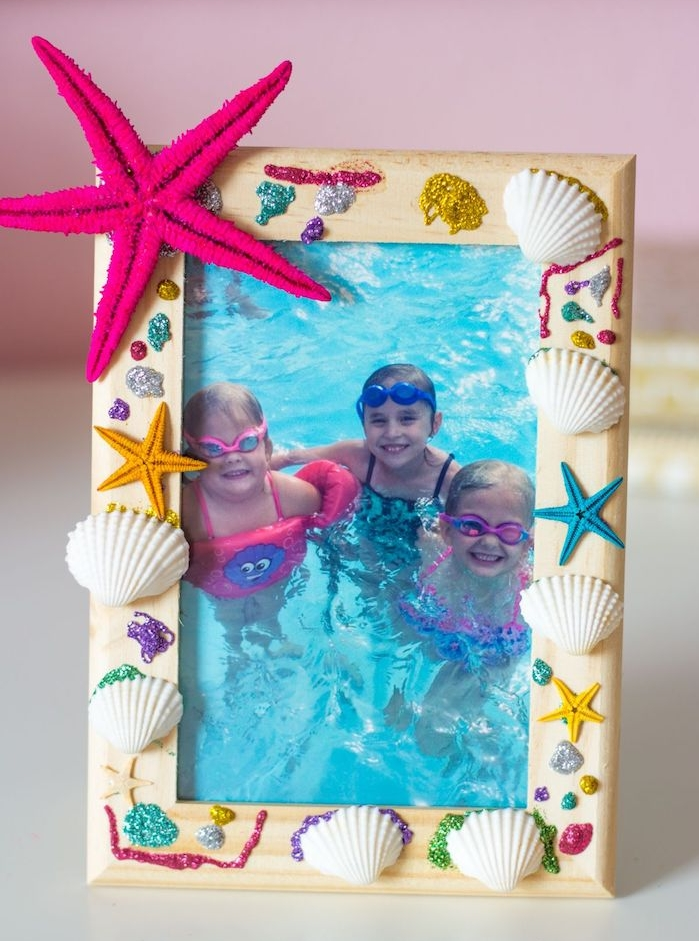 cadre photo diy en bois décoré e coquilles de mer, motif étoile de mer artificielle et des paillettes colorées, activité manuelle primaire