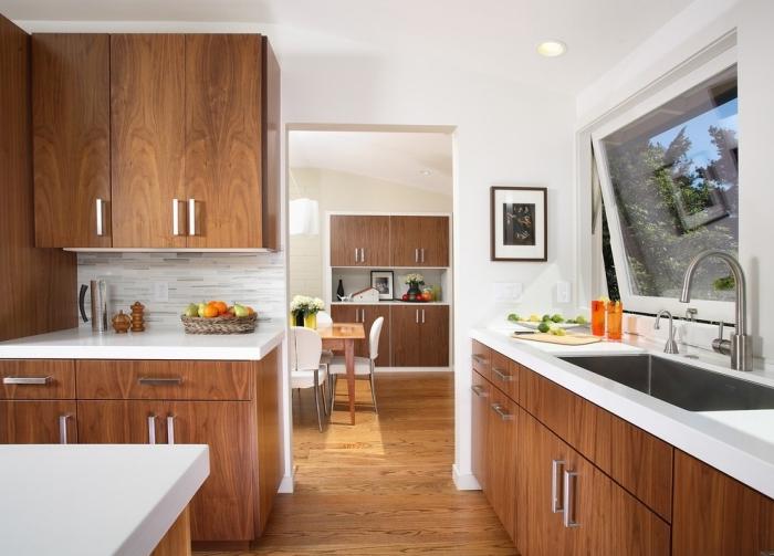 exemple cuisine équipée aux murs blancs et parquet bois marron avec meubles armoires en bois foncé et comptoirs blancs