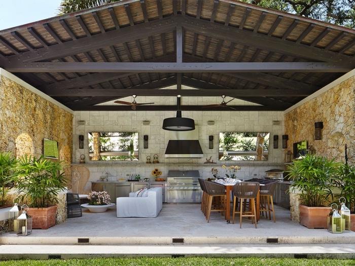 modele de cuisine aménagée dans le jardin avec toit de bois massif foncé et murs en pierre, salon de jardin avec canapé blanc