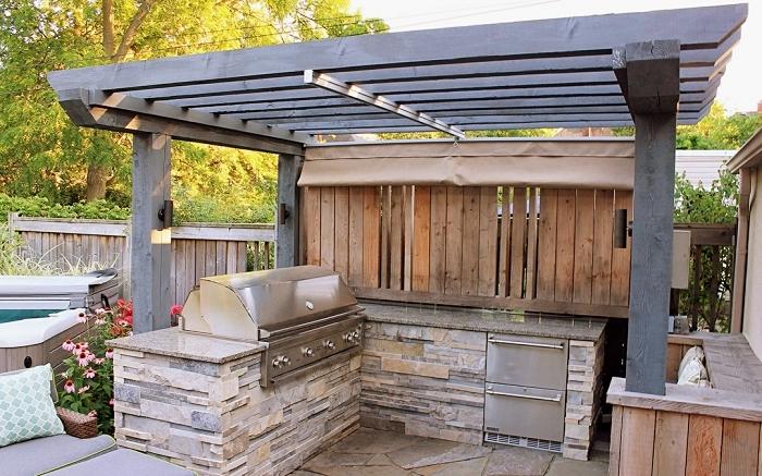 idée pour aménager une cuisine d'extérieur avec toit de bois foncé et ilot en pierre, modèle de barbecue acier inoxydable