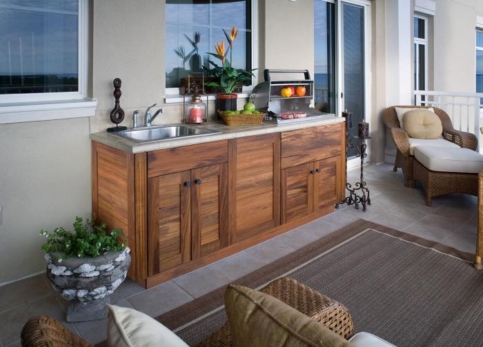 petite cuisine aménagée sur une terrasse avec meubles de bois solide et de rotin, exemple ilot cuisine en bois et inox