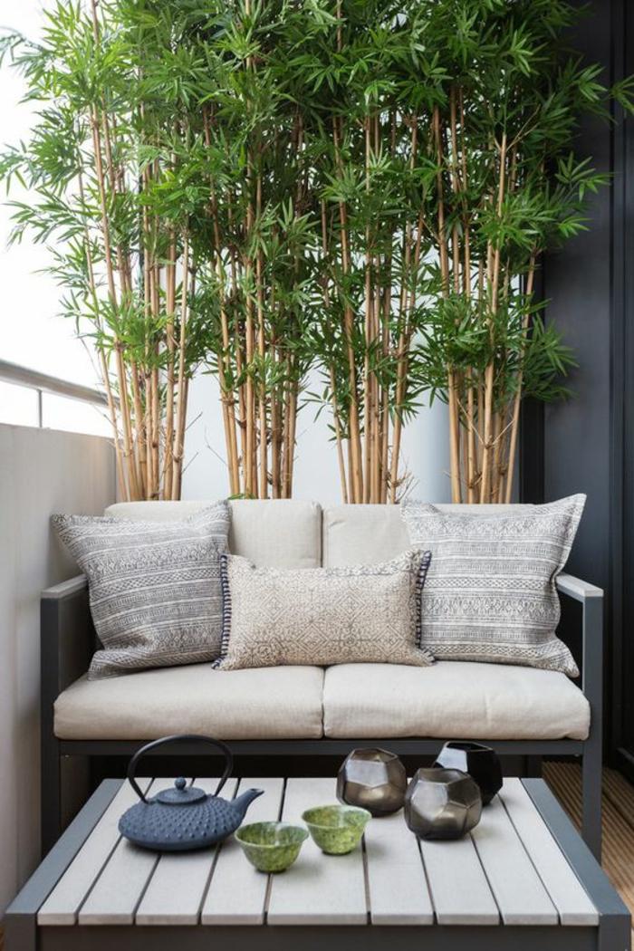 terrasse d'appartement, décoration d'un mur avec des cannes de bambou vertes, aménagement extérieur maison avec canapé trois places et pleins de coussins de taille diverse, petite table basse carrée en bois PVC blanc et bleu canard