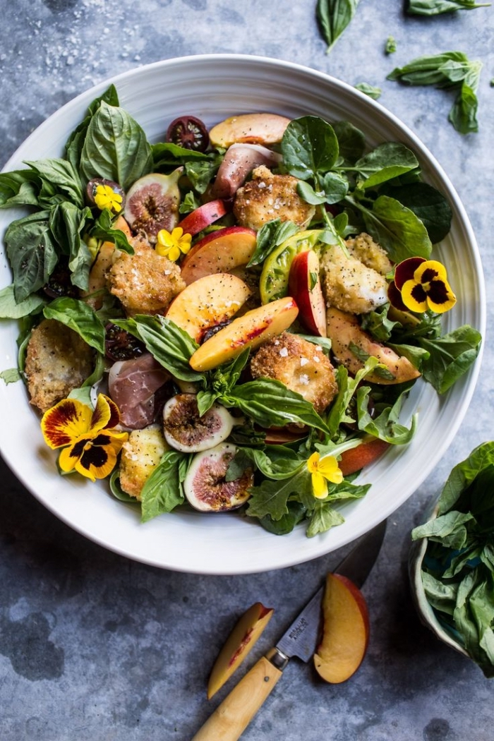 idée originale d'une salade composée été d'épinards, néctarines, figues et mozzarella panée, décorée de fleurs