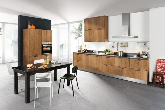 modèle de cuisine tendance au carrelage de sol gris et plafond blanc avec meubles de bois brut foncé et table noire