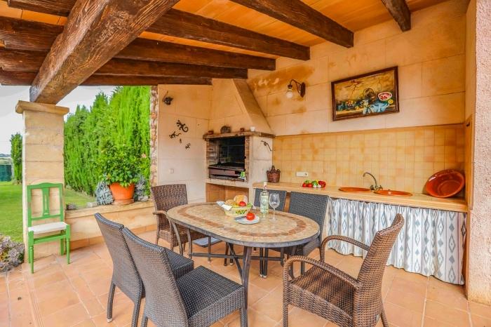 déco de style campagne dans une cuisine de jardin couverte avec toit de poutres bois massif et crédence au carrelage beige