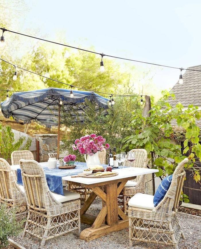 exemple de salle à manger extérieure, amenagement terrasse exterieure avec table bois brut, chaises en rotin, parasol bleu et blanc, vase de fleurs, guirlande lumineuse