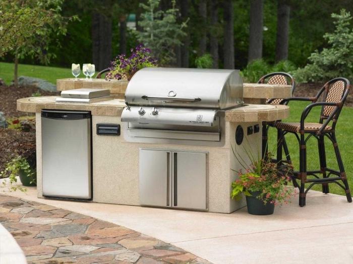 mini cuisine d'été avec équipement frigo et barbecue en acier inoxydable, idée comment aménager une petite cuisine de jardin