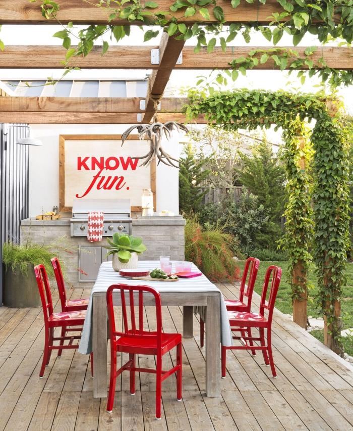 aménager une cuisine de jardin avec gril d'extérieur en acier inoxydable, déco de jardin avec chaises rouges et tableau blanc au cadre bois