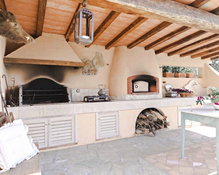 exemple de cuisine d été couverte avec toit de bois massif et sol en larges pierres, déco de cuisine de style rustique et campagnard