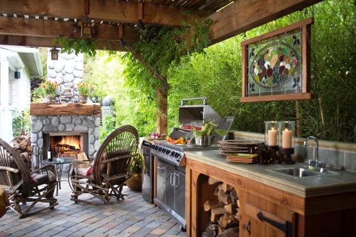 cuisine aménagée de style rustique avec toit de bois et cheminée en pierre, idée choix de barbecue en acier inoxydable