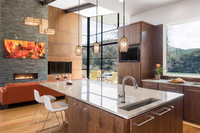 design intérieur moderne dans une cuisine ouverte vers le salon aménagée avec meubles bois foncé et ilot central