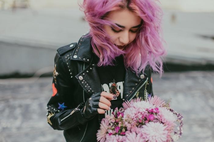 coiffure de style grunge avec racines foncées et coloration de nuance rose pastel et rose foncé, modèle de veste en cuir noir avec décoration étoiles et studs