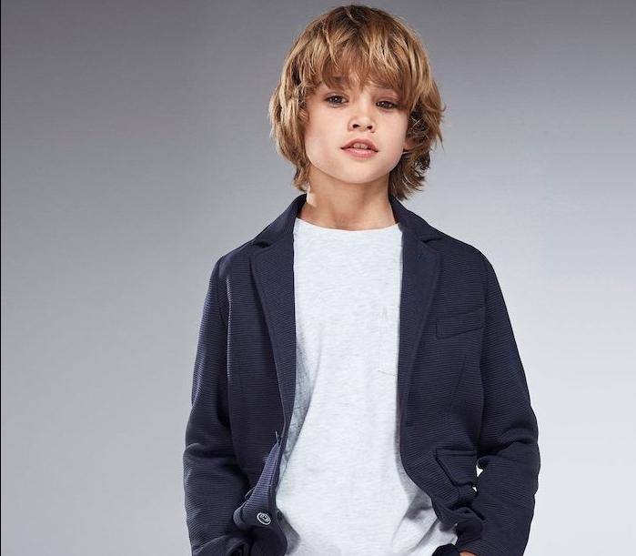 coiffure garcon, style grunge, cheveux blond décoiffés avec une frange sur le front, veste gris anthracite, tee shirt gris clair