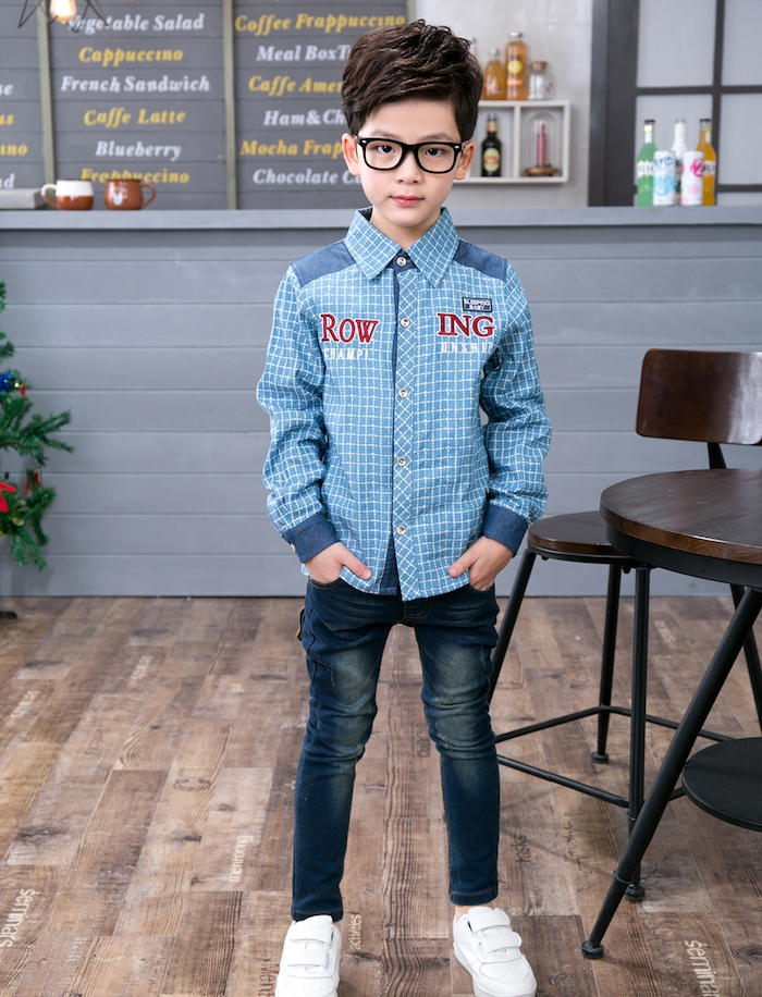 cheveux chatain volumineux avec des boucles fines et frange de coté, chemise bleue, jean, lunettes de vue avec monture noire
