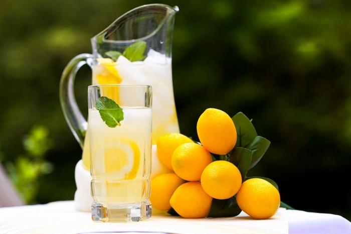 pichet et verre de cocktail rempli de citronnade fraîche à la base d'eau froide glaçons et jus de citron pressé
