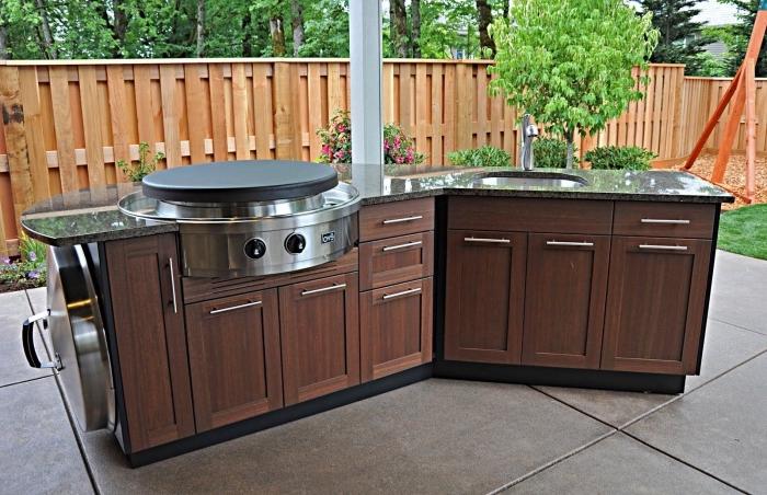 exemple de mini cuisine de jardin avec équipement en acier plan de travail en granite et armoires de bois foncé