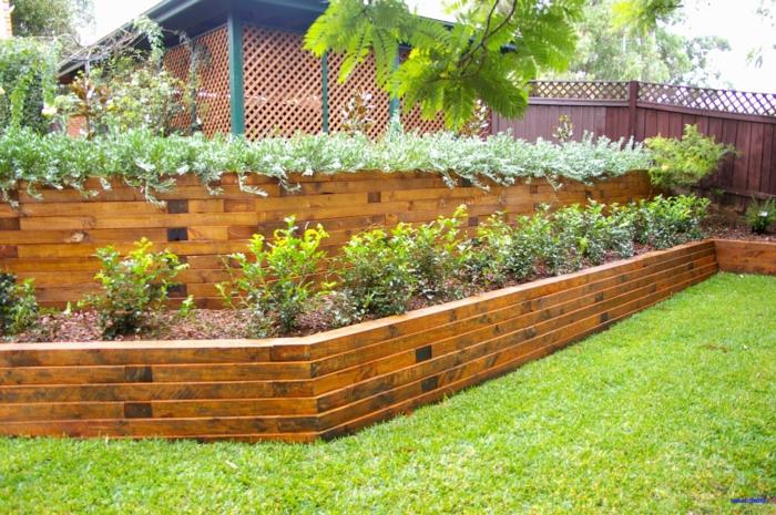 mur vegetal en palette, mur en briques rouges et marron, avec des plantes vertes buissons cloison végétale, coin de jardin avec pelouse impeccable