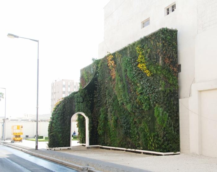 mur vegetal exterieur avec un arc avec une porte blanche, installation en vert, jaune et marron, culture verticale, élément complémentaire d'un immeuble aux murs blancs