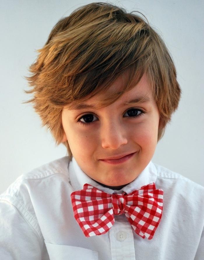 coupe enfant garcon simple, cheveix avec différentes longueurs peignés de coté, mèche asymétrique, chemise blanche, noeud de papillon rouge et blanc