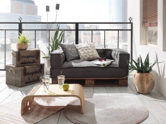 déco de balcon ou terrasse avec matériaux recyclés et plantes vertes, mini canapé en palette de bois foncé avec housse et coussins
