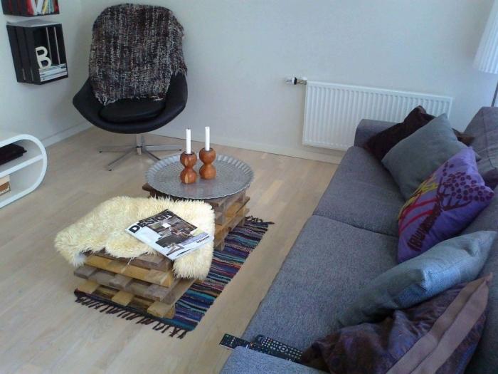 une table basse originale d'esprit scandinave réalisée avec des planches de bois de palette décalées, décorée avec une peau de mouton et un plateau argenté