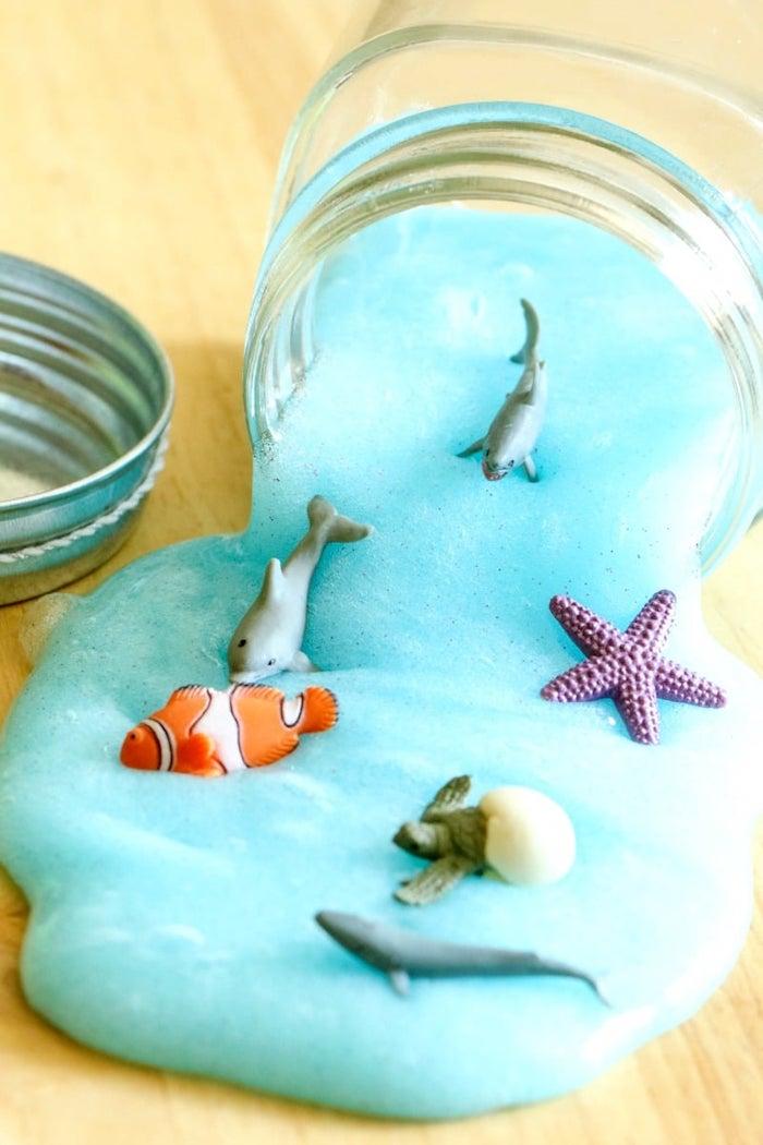 idée pour faire du slime bleu dans un bocal, imitation mer avec des animaux marins, poissons en plastique, activité manuelle 4 ans